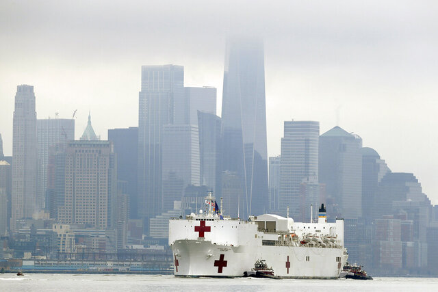 The Navy hospital ship USNS Comfort passes lower Manhattan on its way to docking in New York, Monday, March 30, 2020. The ship has 1,000 beds and 12 operating rooms that could be up and running within 24 hours of its arrival on Monday morning. It's expected to bolster a besieged health care system by treating non-coronavirus patients while hospitals treat people with COVID-19. (AP Photo/Seth Wenig)