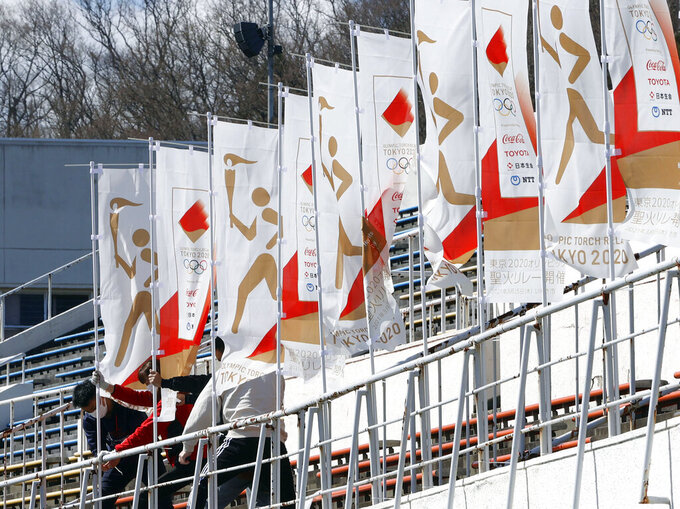 Workers install flags in preparation for the Olympic torch relay, in Iwaki, Fukushima prefecture, northeastern Japan Tuesday, March 23, 2021. The torch relay opens on Thursday from the prefecture. (Fumine Tsutabayashi/Kyodo News via AP)