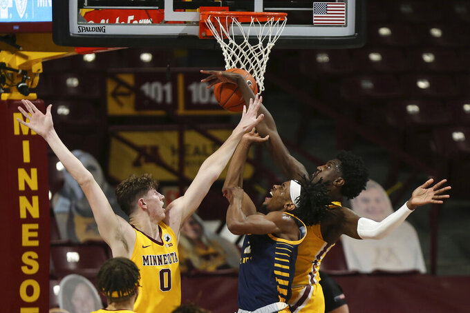 Minnesota forward Isaiah Ihnen, right, fouls UMKC guard Demarius Pitts (2) during the first half of an NCAA college basketball game Thursday, Dec. 10, 2020, in Minneapolis. (AP Photo/Stacy Bengs)