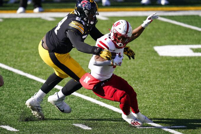Iowa defensive tackle Daviyon Nixon, left, tackles Nebraska wide receiver Wan'Dale Robinson during the first half of an NCAA college football game, Friday, Nov. 27, 2020, in Iowa City, Iowa. (AP Photo/Charlie Neibergall)