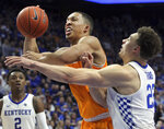 Tennessee's Grant Williams, left, shoots while pressured by Kentucky's Reid Travis during the second half of an NCAA college basketball game in Lexington, Ky., Saturday, Feb. 16, 2019. Kentucky won 86-69. (AP Photo/James Crisp)