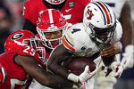 Georgia linebackers Nolan Smith, center, and Quay Walker, left, tackle Auburn running back Tank Bigsby (4) during the second half of an NCAA college football game Saturday, Oct. 3, 2020, in Athens, Ga. (AP Photo/Brynn Anderson)