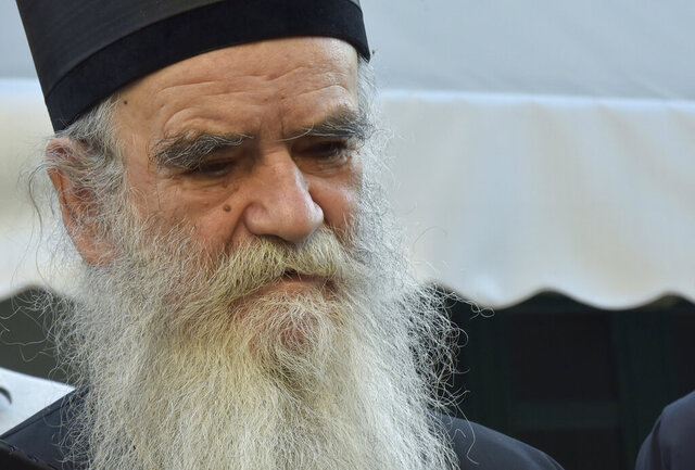 In this photo taken Sunday, Aug. 30, 2020, Serbian Orthodox bishop Amfilohije prepares to vote in parliamentary elections at a polling station in Cetinje, some 30 km south of Podgorica, Montenegro. The head of the Serbian Orthodox Church in Montenegro, which led months of protests against the small Balkan state's pro-Western government, has been hospitalized after testing positive for the coronavirus. (AP Photo/Risto Bozovic)