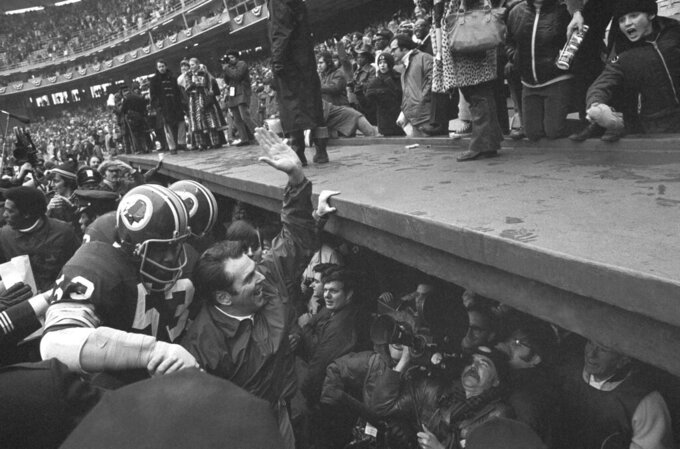 """FILE- In this Dec. 24, 1972, file photo, Washington Redskins coach George Allen waves to fans at Robert F. Kennedy Stadium in Washington as he leaves the field following the team's 16-3 win over the Green Bay Packesr in an NFL playoff game. At left is linebacker Harold McLinton. Washington's NFL team will get rid of the name """"Redskins"""" on Monday, July 13, according to multiple reports. It's unclear when a new name will be revealed for one of the league's oldest franchises. The team launched a """"thorough review"""" of the name July 3.(AP Photo, File)"""