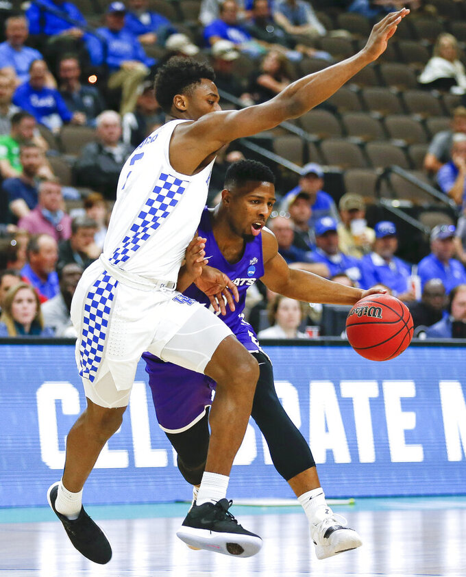 Abilene Christian's Jaylen Franklin, right, looks for a way around Kentucky's Ashton Hagans during the first half of a first-round game in the NCAA men's college basketball tournament in Jacksonville, Fla., Thursday, March 21, 2019. (AP Photo/Stephen B. Morton)