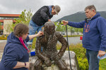 FILE - In this June 30, 2020, file photo, Sitka Historical Society Museum curator Nicole Fiorino, left, tribal council member Bob Sam, center, and museum executive director Hal Spackman clean the statue of Alexander Baranov in Sitka, Alaska. The Sitka Assembly voted July 14 to relocate the statue to the museum. Baranov, who founded the city in 1804 on a site already inhabited by Alaska Natives, was known as a brutal colonialist who murdered and enslaved Alaska Native people before the United States purchased Alaska from Russia in 1867. (James Poulson/The Daily Sitka Sentinel via AP, File)