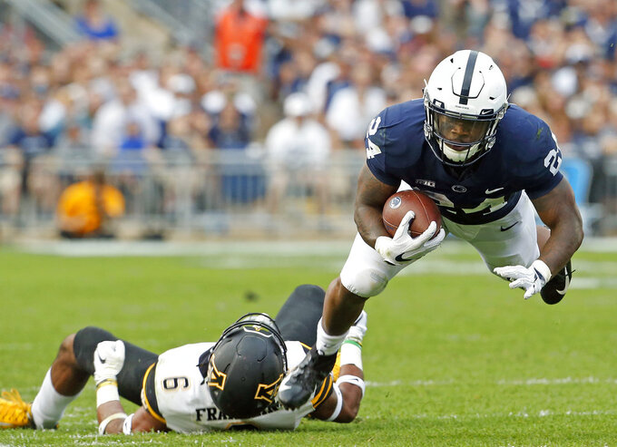 Penn State's Miles Sanders (24) dives for extra yardage after being tackled by Appalachian State's Desmond Franklin (6) during the second half of an NCAA college football game in State College, Pa., Saturday, Sept. 1, 2018. Penn State won 45-38 in OT. (AP Photo/Chris Knight)