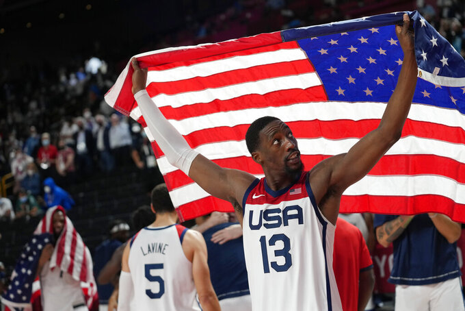 United States' Bam Adebayo (13) waves the United States flag as he celebrates with teammates after their win over France in a men's basketball Gold medal game at the 2020 Summer Olympics, Saturday, Aug. 7, 2021, in Saitama, Japan. (AP Photo/Eric Gay)
