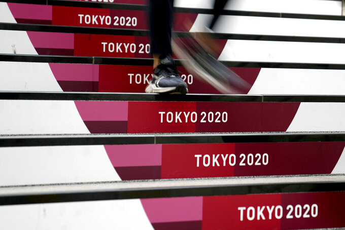 A commuter walks down stairs leading to a subway station before the start of the 2020 Summer Olympics, Wednesday, July 21, 2021, in Tokyo. (AP Photo/Jeff Roberson)