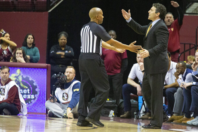 The referee talks with Georgia Tech head coach Josh Pastner in the second half of an NCAA college basketball game against Florida State in Tallahassee, Fla., Tuesday, Dec. 31, 2019. Florida State defeated Georgia Tech 70-58. (AP Photo/Mark Wallheiser)