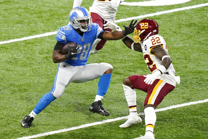Detroit Lions running back Adrian Peterson (28) attempts to push away Washington Football Team safety Deshazor Everett (22) during the first half of an NFL football game, Sunday, Nov. 15, 2020, in Detroit. (AP Photo/Carlos Osorio)