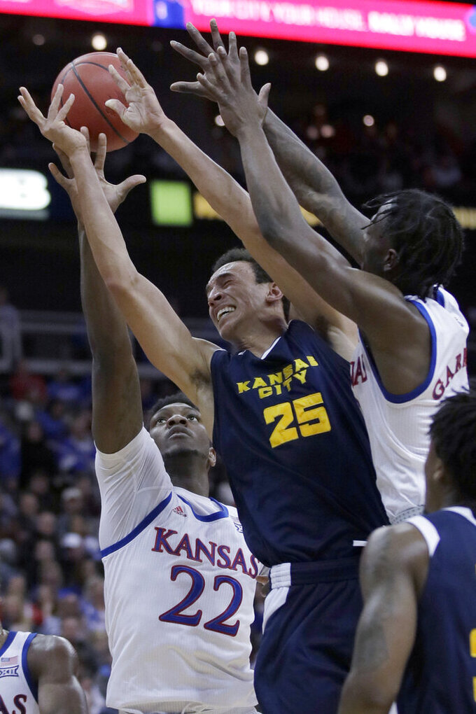 Kansas City forward Javan White (25) tries to shoot while between Kansas defenders Silvio De Sousa (22) and Marcus Garrett, right, during the first half of an NCAA college basketball game in Kansas City, Kan., Saturday, Dec. 14, 2019. (AP Photo/Orlin Wagner)