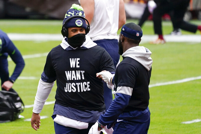 Seattle Seahawks quarterback Russell Wilson (3), left, greeting teammate wide receiver Penny Hart (19) on the field before the start of an NFL football game against the Washington Football Team, Sunday, Dec. 20, 2020, in Landover, MD. (AP Photo/Andrew Harnik)
