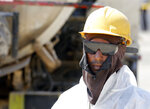 In this photo opportunity during a trip organized by Saudi information ministry, a worker wears safety gear in the Aramco's Khurais oil field, Saudi Arabia, Friday, Sept. 20, 2019, after it was hit during Sept. 14 attack. Saudi officials brought journalists Friday to see the damage done in an attack the U.S. alleges Iran carried out. (AP Photo/Amr Nabil)