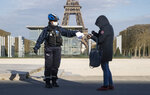 A policewoman wears a mask to protect herself against the spread of the new coronavirus, left, checks the special permission of a residence at the garden of the Eiffel Tower in Paris, Monday, April 6, 2020. For most people, the new coronavirus causes only mild or moderate symptoms, such as fever and cough. For some, especially older adults and people with existing health problems, it can cause more severe illness, including pneumonia. (AP Photo/Michel Euler)
