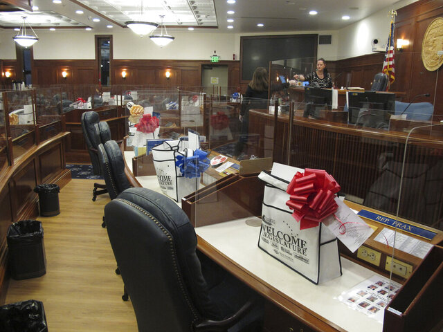 Welcome bags and plexiglass dividers placed around their desks await lawmakers on the Alaska House floor in Juneau, Alaska, Monday, Jan. 18, 2021. The committee was among several that had scheduled meetings Monday, the last day before the new Legislature is set to convene on Tuesday, Jan. 19. (AP Photo/Becky Bohrer)