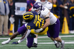Michigan Wolverines running back Hassan Haskins (25) is tackled by Northwestern Wildcats linebacker Bryce Gallagher (32) during the first half of an NCAA college football game, Saturday, Oct. 23, 2021, in Ann Arbor, Mich. (AP Photo/Carlos Osorio)