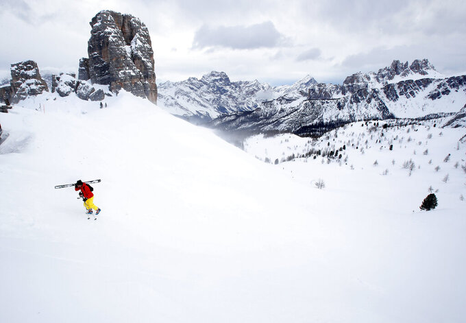 FILE - In this Friday, Jan. 29, 2021 file photo, a skier climbs the hill in Cortina D'Ampezzo, Italy. The natural beauty of Cortina will be of special importance at the alpine ski World championships, with organizers hoping that the images from the slopes beamed around the globe to TV viewers will make up for the lack of fans amid the coronavirus pandemic. (AP Photo/Antonio Calanni, File)