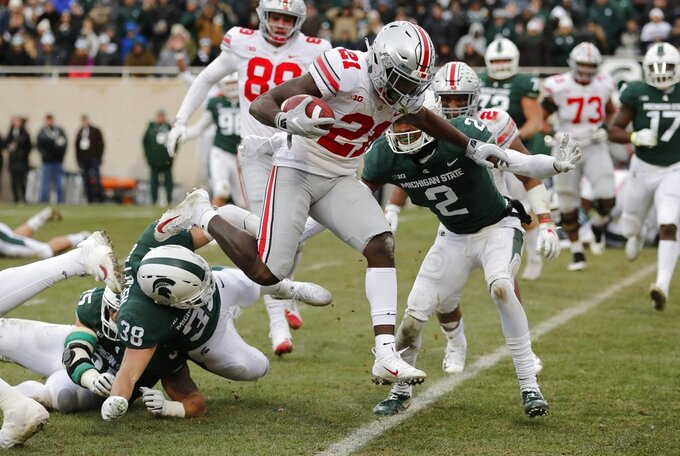 Ohio State wide receiver Parris Campbell (21) leaps over Michigan State linebacker Byron Bullough (38) to score on a 1-yard run during the first half of an NCAA college football game, Saturday, Nov. 10, 2018, in East Lansing, Mich. (AP Photo/Carlos Osorio)