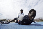 In this Feb. 12, 2020 photo, Abraham Majok, a South Sudanese 1500m runner, trains practice with Japanese volunteers during training for the Tokyo 2020 Olympics in Maebashi, Gunma Prefecture, north of Tokyo. Four South Sudanese athletes are already training in Japan for the Olympics. They are getting a head start. And although they aren't likely to win any medals they will be ahead of most of the other 11,000 athletes who will be in Tokyo this summer for the Olympics. (AP Photo/Eugene Hoshiko)