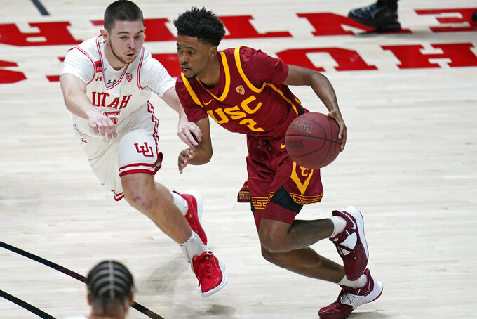 Southern California guard Tahj Eaddy (2) drives around Utah guard Rylan Jones during the first half of an NCAA college basketball game Saturday, Feb. 27, 2021, in Salt Lake City. (AP Photo/Rick Bowmer)