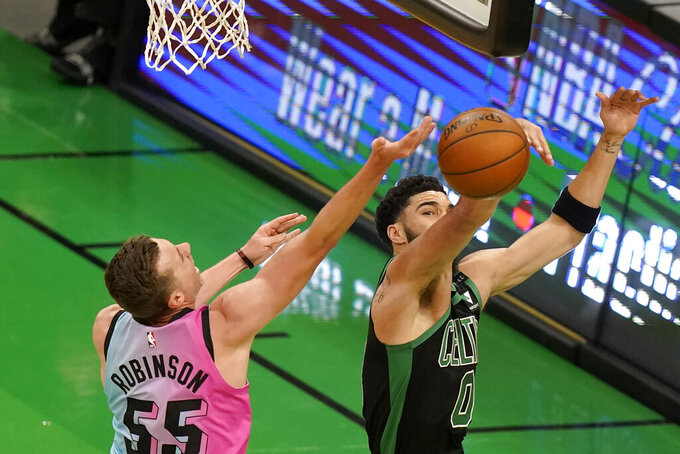 Miami Heat's Duncan Robinson, left, drives toward the basket as Boston Celtics' Jayson Tatum, right, deflects the ball in the first half of a basketball game, Sunday, May 9, 2021, in Boston. (AP Photo/Steven Senne)