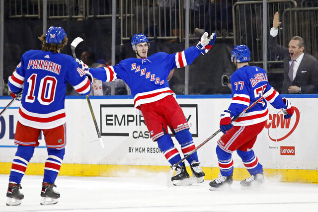 New York Rangers left wing Artemi Panarin (10) and defenseman Tony DeAngelo (77) celebrate with left wing Chris Kreider (20) after Kreider scored a goal during the first period of the team's NHL hockey game against the New Jersey Devils, Thursday, Jan. 9, 2020, in New York. (AP Photo/Kathy Willens)