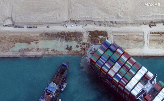 This satellite image from Maxar Technologies shows excavation work in an atempt to free the cargo ship MV Ever Given that is stuck in the Suez Canal near Suez, Egypt, Sunday, March 28, 2021. Two additional tugboats sped Sunday to Egypt's Suez Canal to aid efforts to free the skyscraper-sized container ship wedged for days across the crucial waterway, even as major shippers increasingly divert their boats out of fear the vessel may take even longer to free. (©Maxar Technologies via AP)