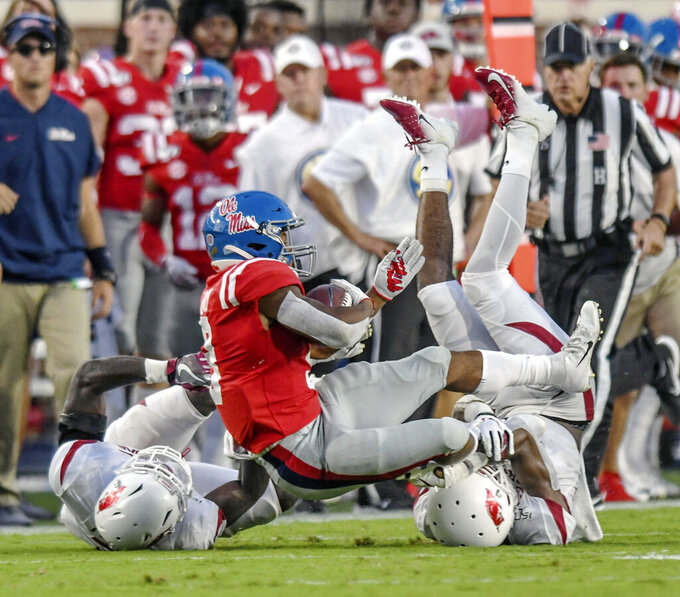 Mississippi running back Jerrion Ealy (9) is tackled by Arkansas defensive backs Joe Foucha (7) and Jarques McClellion (4) during the first half of an NCAA college football game, Saturday, Sept. 7, 2019, in Oxford, Miss. (Bruce Newman/The Oxford Eagle via AP)