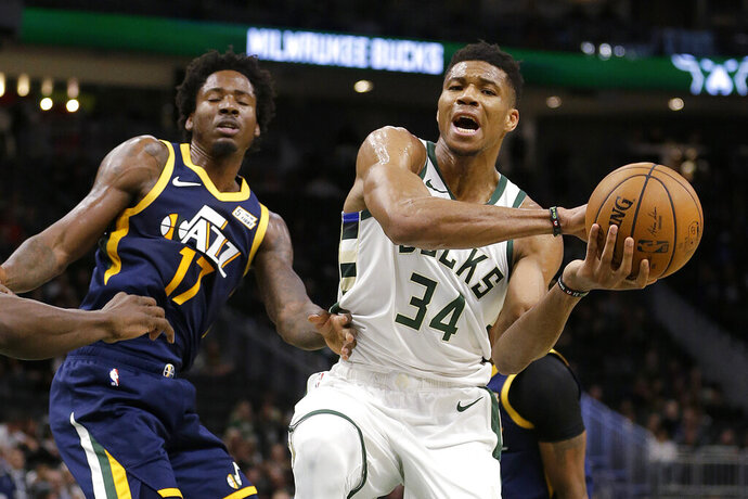 Milwaukee Bucks' Giannis Antetokounmpo (34) drives to the basket against Utah Jazz's Ed Davis during the first half of a preseason NBA basketball game Wednesday, Oct. 9, 2019, in Milwaukee. (AP Photo/Aaron Gash)