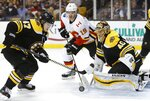 Boston Bruins' Torey Krug (47) moves to clear the puck after a shot by Calgary Flames' Matthew Tkachuk (19) on Tuukka Rask (40), of Finland, during the third period of an NHL hockey game in Boston, Tuesday, Feb. 13, 2018. The Bruins won 5-2. (AP Photo/Michael Dwyer)