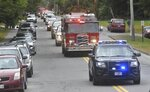 A Farmington fire truck leads the leads a procession honoring Farmington Fire Rescue Capt. Michael Bell as it arrives in Farmington, Maine, Tuesday, Sept. 17, 2019. Bell was killed in an explosion the day before that also injured six other firefighters and a maintenance worker at the LEAP building, a nonprofit that serves people with cognitive and intellectual disabilities in Farmington. (Rich Abrahamson/The Central Maine Morning Sentinel via AP)
