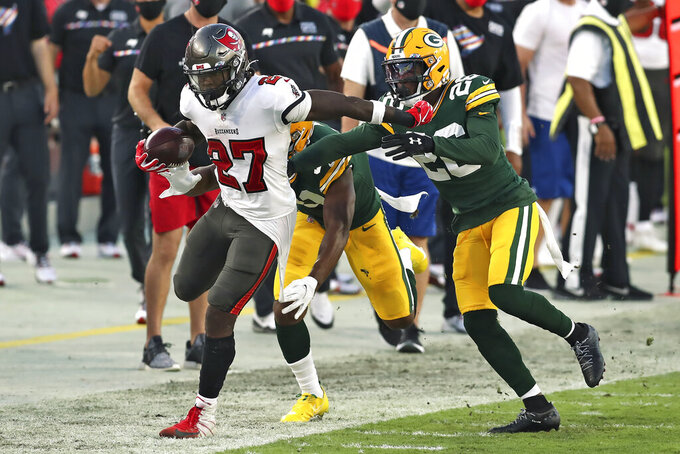 Tampa Bay Buccaneers running back Ronald Jones II (27) gets pushed out of bund by Green Bay Packers free safety Darnell Savage (26) during the second half of an NFL football game Sunday, Oct. 18, 2020, in Tampa, Fla. (AP Photo/Mark LoMoglio)