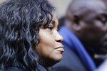 Tamara Lanier listens as attorney Benjamin Crump, right, speaks during a news conference near the Harvard Club Wednesday, March 20, 2019, in New York. Lanier, of Norwich, Conn., is suing the Harvard University for