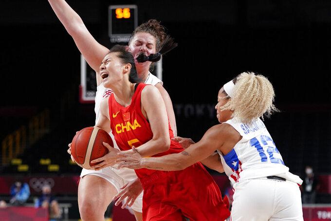 China's Siyu Wang (5) drives between Puerto Rico's Sabrina Lozada-Cabbage and Dayshalee Salaman (12) during a women's basketball preliminary round game at the 2020 Summer Olympics in Saitama, Japan, Tuesday, July 27, 2021. (AP Photo/Charlie Neibergall)