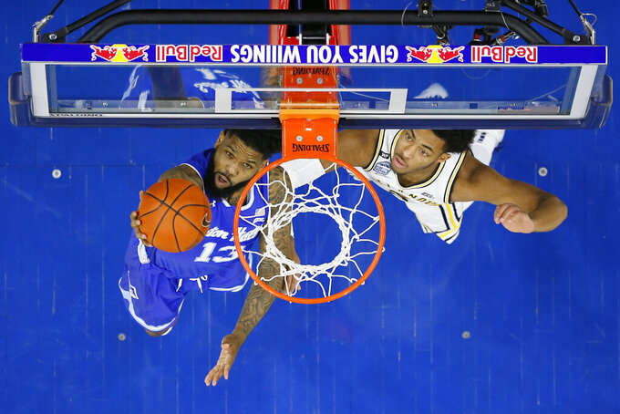 Seton Hall's Myles Powell, left, goes up for a shot past Villanova's Justin Moore during the first half of an NCAA college basketball game, Saturday, Feb. 8, 2020, in Philadelphia. (AP Photo/Matt Slocum)