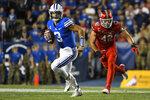 Brigham Young quarterback Jaren Hall (3) runs past Utah defensive end Mika Tafua (42) during the first half of an NCAA college football game Saturday, Sept. 11, 2021, in Provo, Utah. (AP Photo/Alex Goodlett)