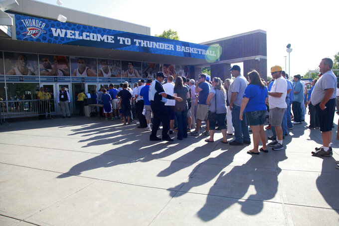FILE - In this June 12, 2012, file photo, fans line up in front of Chesapeake Arena before Game 1 of the NBA finals basketball series between the Oklahoma City Thunder and the Miami Heat, in Oklahoma City. It used to be that empty seats caused palpitations in team owners and college administrators relying on ticket sales and concessions to beef up the profit margins. Now, those empty seats – and short lines and clear concourses – will be the norm for a while as sports grapples with social distancing requirements. (AP Photo/Jeff Roberson, File)