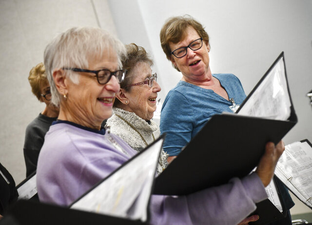 In this Oct. 29, 2019 photo, singers smile while performing a piece during a Musical Memory Makers rehearsal, at the Whitney Senior Center in St. Cloud, Minn. (Dave Schwarz/St. Cloud Times via AP)