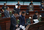 Pro-democracy lawmakers pay a silent tribute to the man who fell to his death on Saturday evening after hanging a protest banner on scaffolding on a shopping mall at the Legislative Council in Hong Kong, Wednesday, June 19, 2019. Hong Kong lawmakers are meeting for the first time in a week, after massive protests over an extradition bill that eventually was suspended. (AP Photo/Vincent Yu)