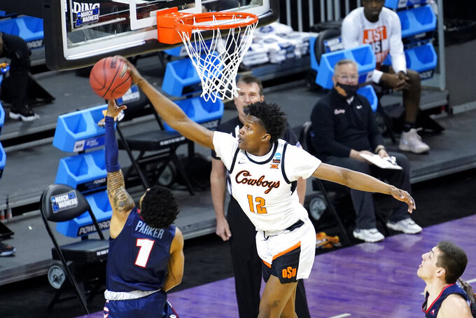 Oklahoma State forward Matthew-Alexander Moncrieffe (12) blocks the shot of Liberty's Chris Parker during the first half of a first round NCAA college basketball game Friday, March 19, 2021, at the Indiana Farmers Coliseum in Indianapolis. (AP Photo/Charles Rex Arbogast)