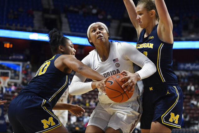 Florida State's Kiah Gillespie, center, is fouled by Michigan's Naz Hillmon, left, as Michigan's Izabel Varejão, right, defends in the second half of an NCAA college basketball game, Sunday, Dec. 22, 2019, in Uncasville, Conn. (AP Photo/Jessica Hill)