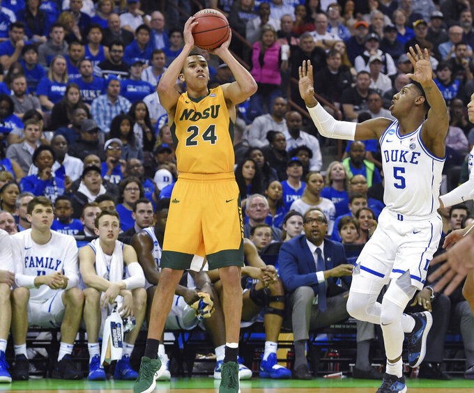 North Dakota State's Tyson Ward (24) shoots a 3-pointer while defended by Duke's RJ Barrett (5) during the first half of a first-round game in the NCAA men's college basketball tournament in Columbia, S.C. Friday, March 22, 2019. (AP Photo/Richard Shiro)
