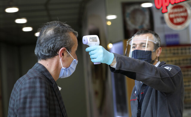 A security official wearing a face mask for protection against the coronavirus, checks a customer's temperature at entry of popular Karum shopping mall, in Ankara, Turkey, Monday, May 11, 2020. Shopping malls, barber shops, hairdressers and beauty salons have reopened for business across Turkey for the first time in seven weeks as the country gradually eases restrictions aimed to prevent the spread of the new coronavirus.(AP Photo/Burhan Ozbilici)