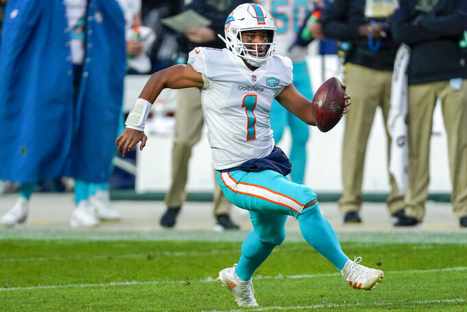 Miami Dolphins quarterback Tua Tagovailoa (1) runs against the Denver Broncos during an NFL football game Sunday, Nov. 22, 2020, in Denver. The focus is on the matchup between Patrick Mahomes and Tua Tagovailoa, even though there's no debate about which quarterback is better. The Miami Dolphins might have the superior defense, however, which lends intrigue to Sunday's game against the Kansas City Chiefs.(AP Photo/Jack Dempsey)