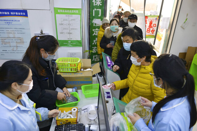 People line up to buy face masks at a drug store in Nanjing in eastern China's Jiangsu Province, Wednesday, Jan. 29, 2020. Countries began evacuating their citizens Wednesday from the Chinese city hardest-hit by an outbreak of a new virus that infected more than 6,000 on the mainland and abroad. (Chinatopix via AP)