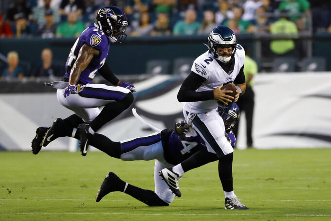 Philadelphia Eagles' Cody Kessler (2) is tackled by Baltimore Ravens' Patrick Onwuasor (48) and Brandon Carr (24) during the first half of a preseason NFL football game Thursday, Aug. 22, 2019, in Philadelphia. (AP Photo/Michael Perez)