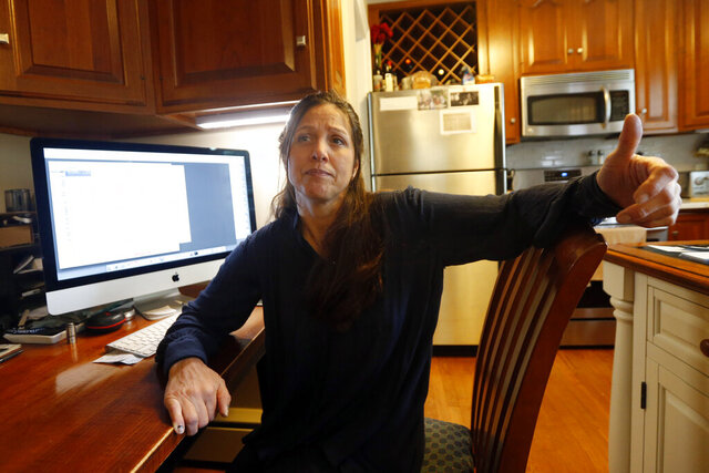 In this Thursday, April 23, 2020 photo, Laura Campbell speaks as she looks over vacation rental agreements at her home in Richmond, Va. Campbell lost deposits and rental fees when after cancelling vacations due to COVID-19 despite having travel insurance. (AP Photo/Steve Helber)
