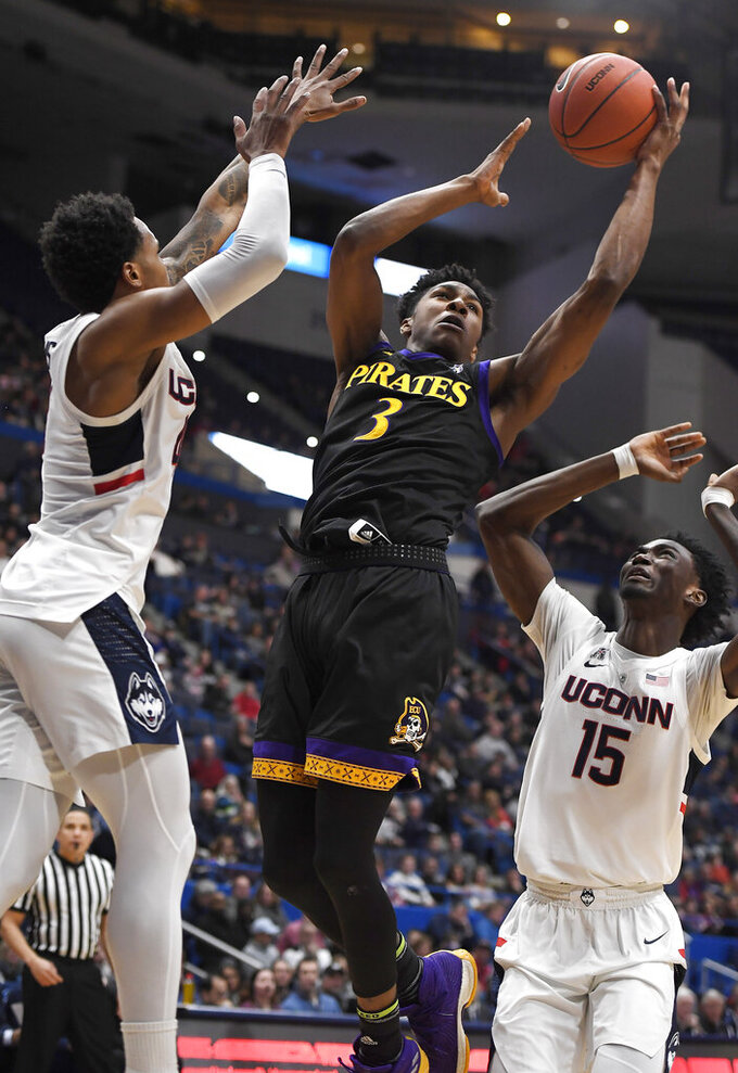 East Carolina's Seth LeDay (3) makes a basket between Connecticut's Jalen Adams (4) and Sidney Wilson (15) during the first half of an NCAA college basketball game, Sunday, Feb. 3, 2019, in Hartford, Conn. (AP Photo/Jessica Hill)