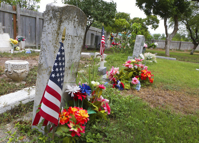 The grave of WWII U.S. Army soldier rest along with other family members at Jackson Ranch Cemetery Monday, Sept. 10, 2018, in Pharr, Texas. More than a year after tireless efforts to save the cemetery and church, which included working with congressional members to introduce legislation that would support their cause, the property is once again in danger of being bordered off by planned construction. (Joel Martinez/The Monitor via AP)